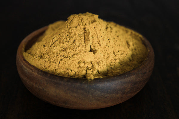 Fresh grinded yellow turmeric root powder shown in a wooden bowl