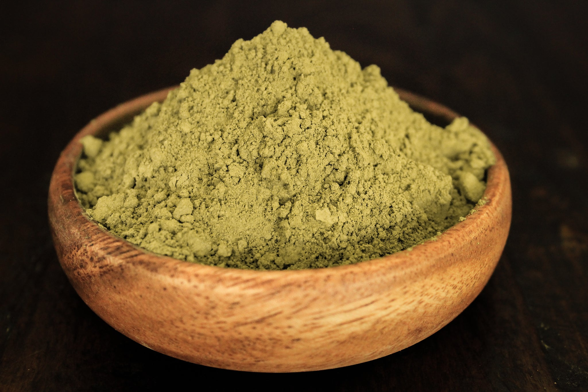 Pure natural white sumatra kratom powder in a wooden bowl