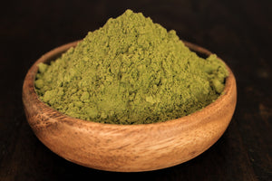 White Hulu fine kratom powder in a wooden bowl