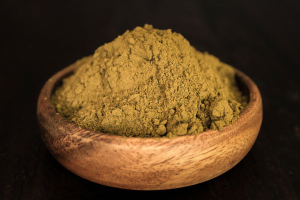 Yellow Sumbawa grinded kratom leaf powder in close up wooden bowl