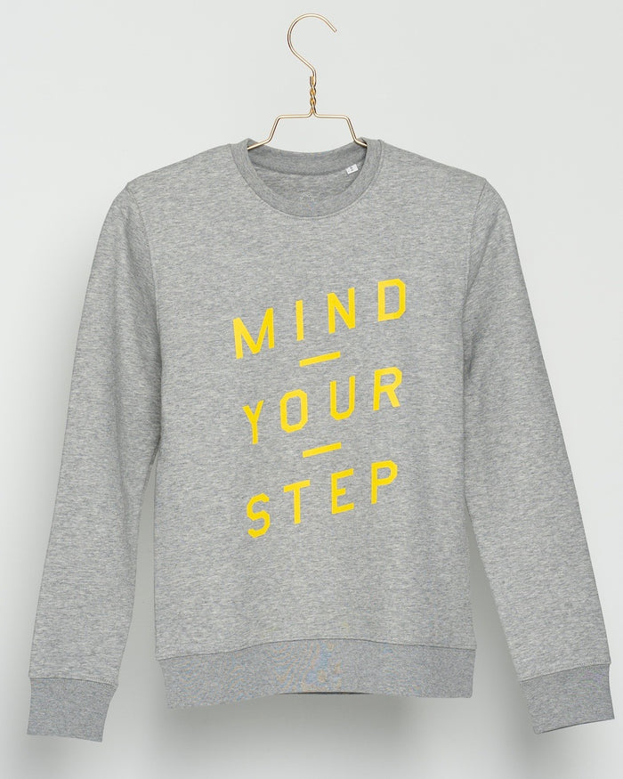 "THE NEW COLLECTION. ""Mind Your Step"". Unisex Sweater. Crew Neck. Heather Grey."