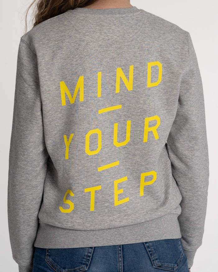 "SPECIAL EDITION! Full colour logo on the front! ""Mind Your Step"" on the back! Unisex Sweater, Crew Neck, Heather Grey."