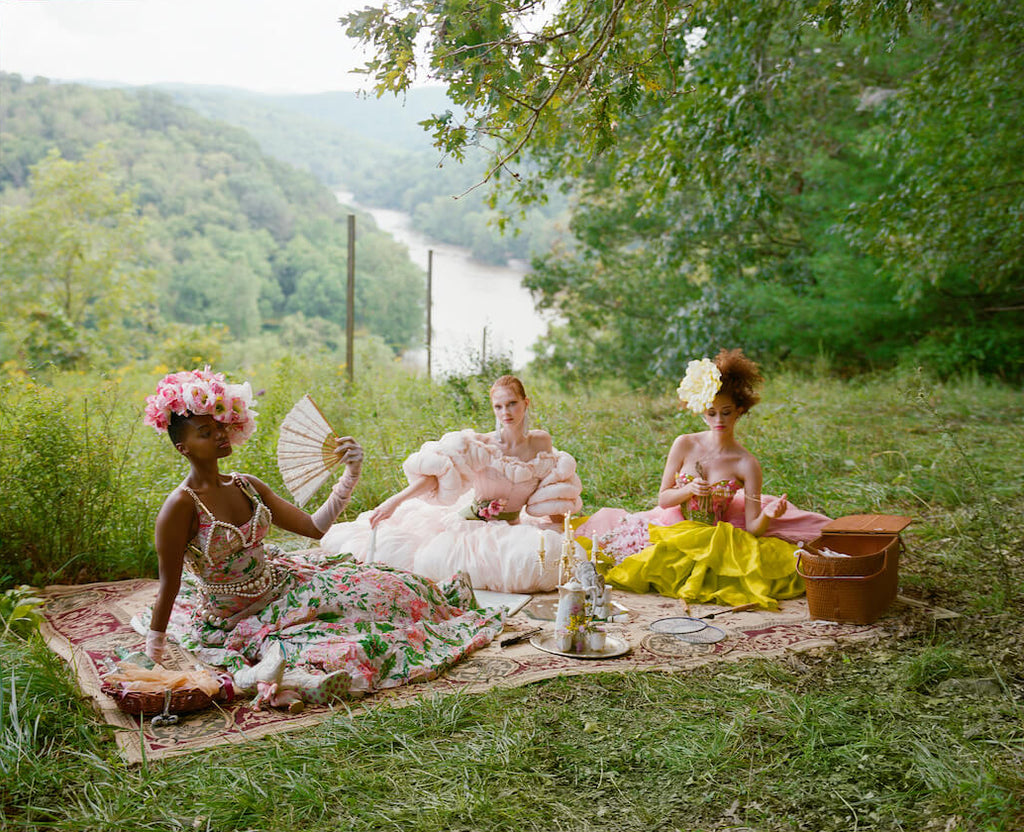 High fashion picnic in countryside with decadent corsets, ruffled dresses and parasols