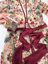 Closeup details of silk satin robe with couture embroidered flowers