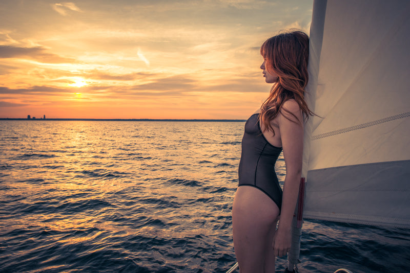 Model in a black lace designer bodysuit with a sunset over the ocean