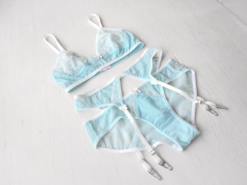 Fancy designer lingerie set in light blue mesh with suspender belt