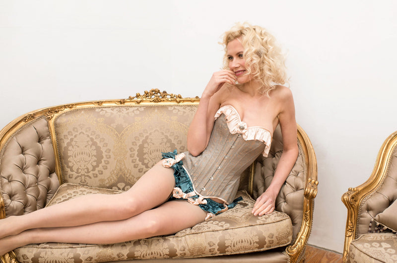 Retro corset and lingerie on a settee with grey blue silk ruffled panties and nylons