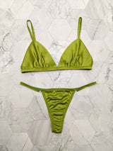 Luxury, designer lingerie set in green silk satin, including a bralette and thong