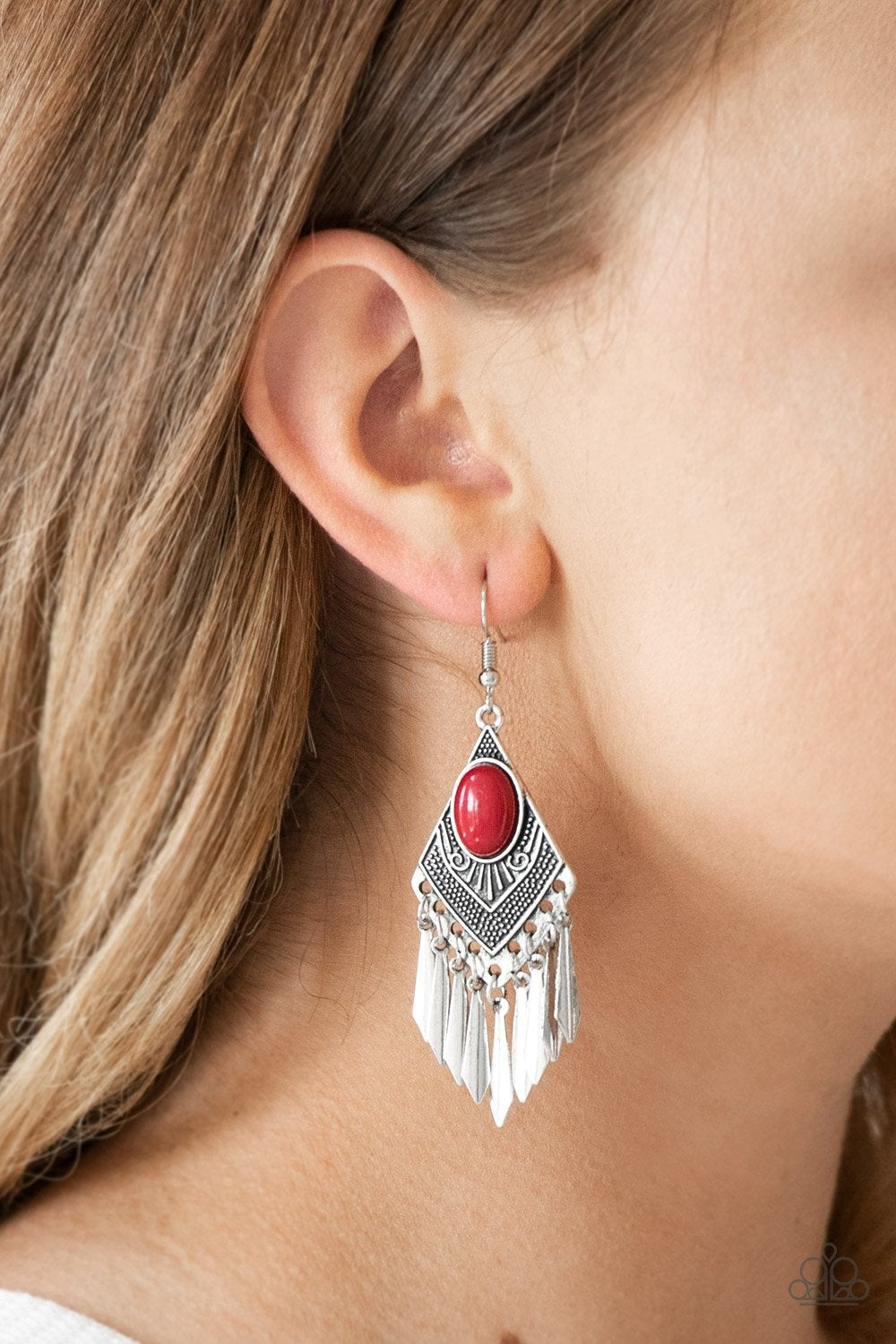 A polished red bead is pressed into a diamond shaped frame radiating with tribal inspired details. Flared silver bars swing from the bottom of the ornate lure, creating a shiny fringe. Earring attaches to a standard fishhook fitting.