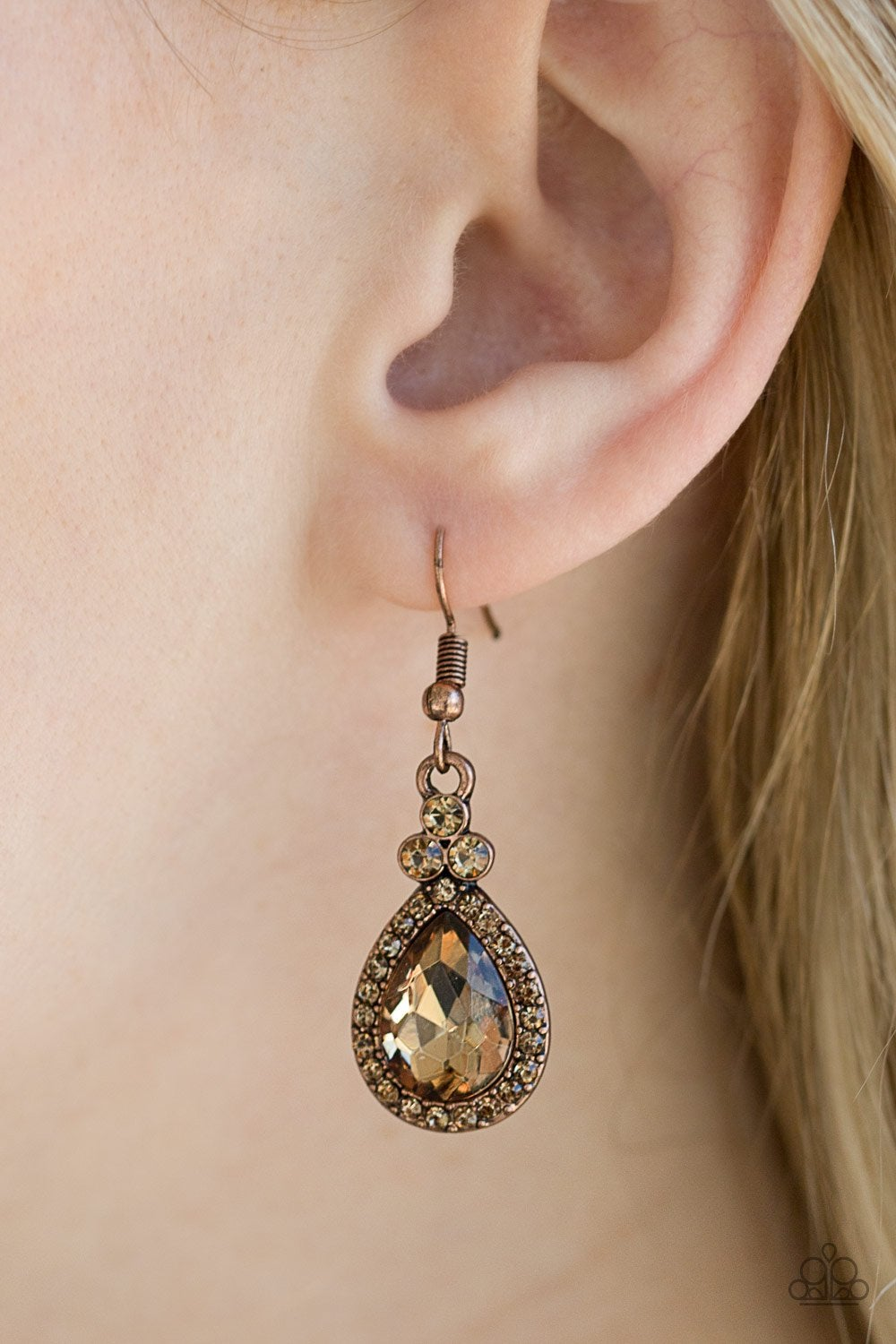 A glittery topaz teardrop gem is pressed into a topaz rhinestone encrusted frame, creating a timeless lure. Earring attaches to a standard fishhook fitting.
