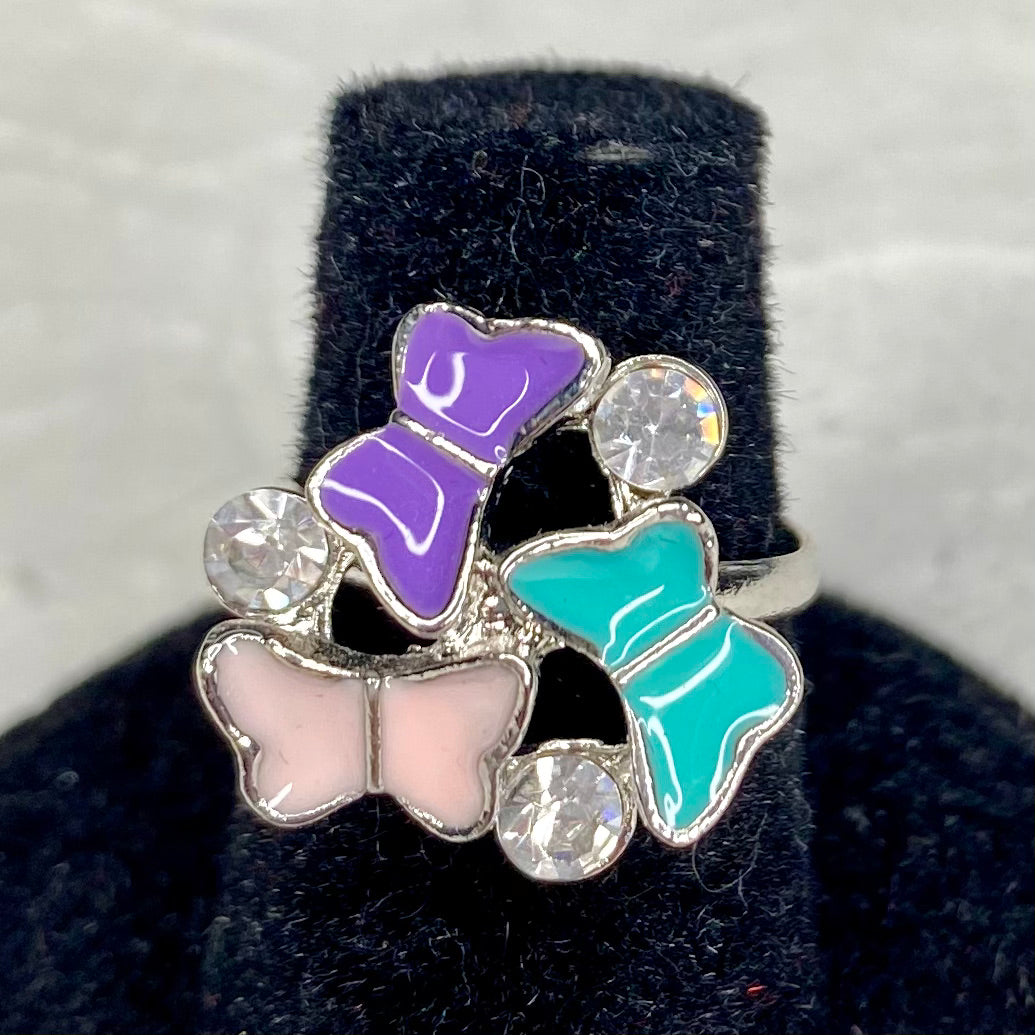 3 enamel butterflies in purple, pink and aqua, surrounded by white gemstones on an adjustable silver band.