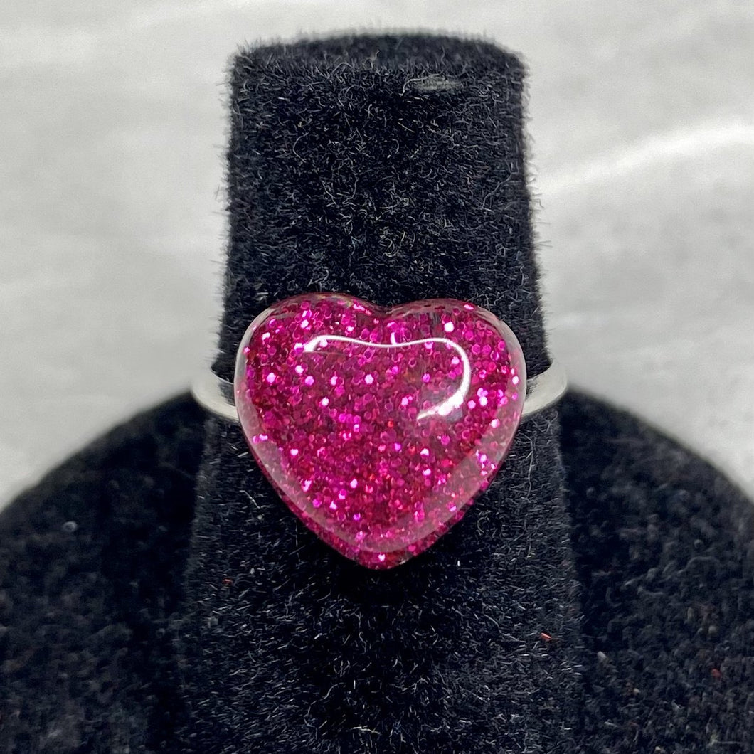 Hot pink glitter heart on an adjustable silver ring.