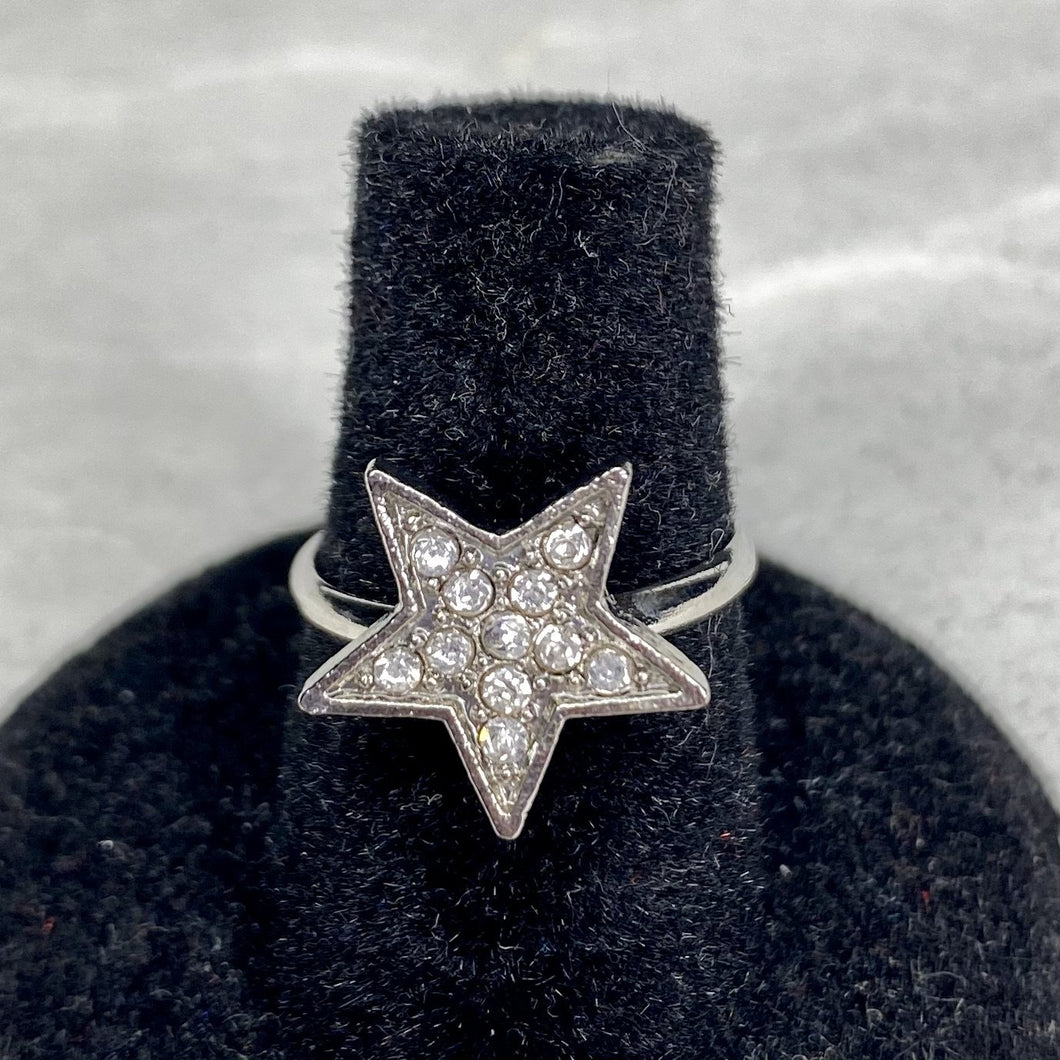 Silver super star embedded with white gemstones on an adjustable silver band.