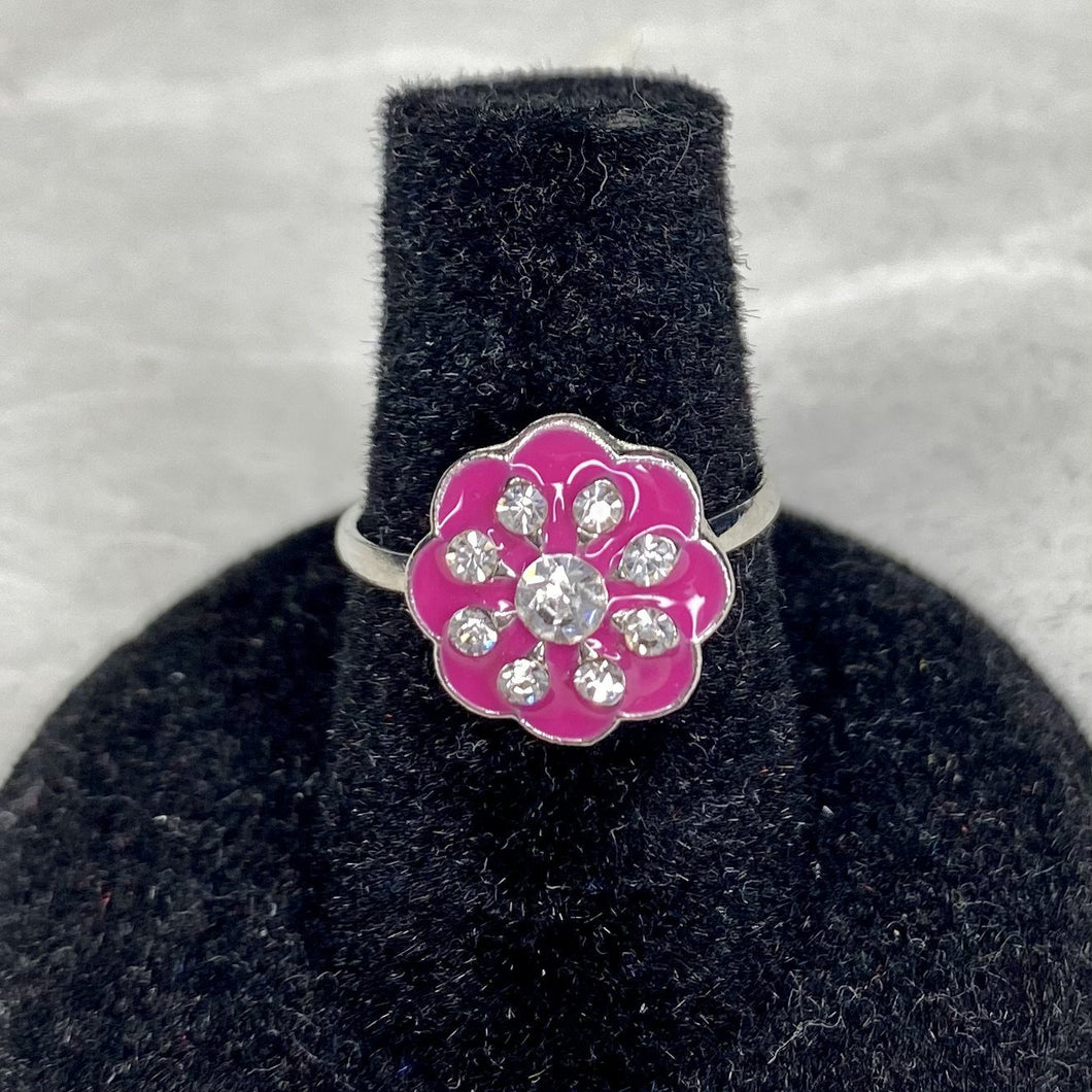 Bright pink enamel petals surround white gemstones in a floral pattern on an adjustable silver band.