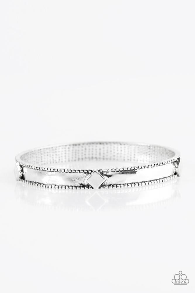 Tilted silver squares are pressed into an antiqued silver bangle for a tribal inspired look.
