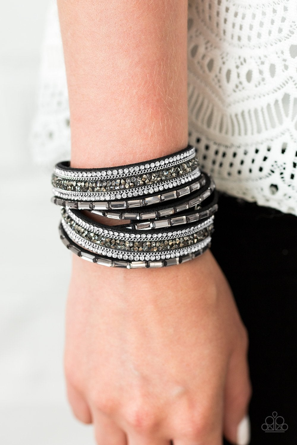 Varying in cut and shimmer, glittery white, smoky, and hematite rhinestones are sprinkled along black suede bands for a sassy look. The elongated design allows for a trendy double wrap around the wrist. Features an adjustable snap closure.
