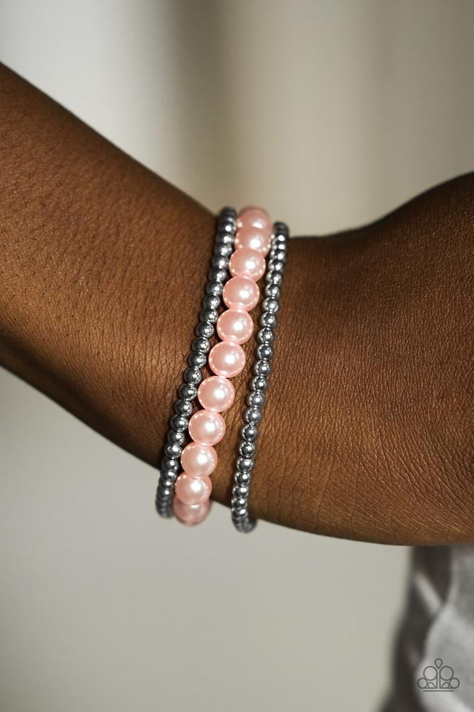Infused with two strands of classic silver beading, pearly pink beads are threaded along an elastic stretchy band. Rhinestone encrusted rings are sprinkled between the pearl accents for a refined finish.