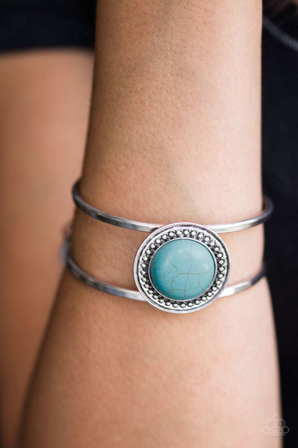 Two silver bars curl around the wrist, creating an airy cuff. Brushed in an antiqued finish, silver studs dance around a refreshing turquoise stone for a chic Southwestern inspired style.
