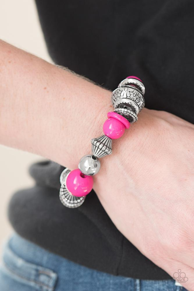 Embossed in a whimsical floral pattern, chunky silver beads, mismatched silver accents, and vivacious pink beads are threaded along an elastic stretchy band for a seasonal look.