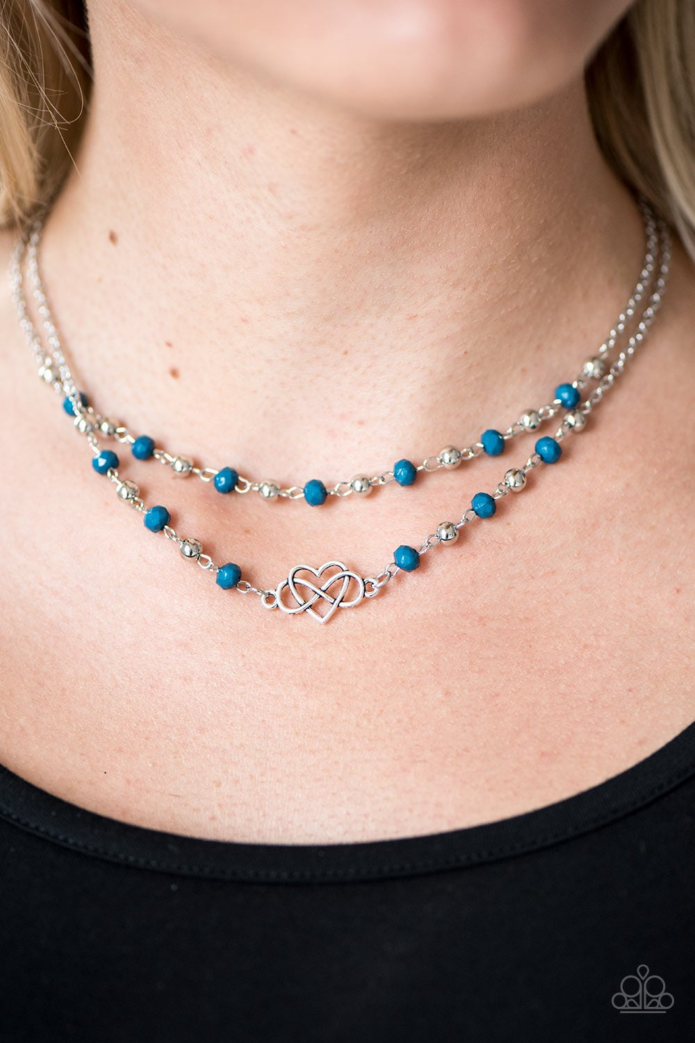 Faceted blue and shiny silver beads trickle along two strands of shimmery silver chain, creating colorful layers beneath the collar. A shimmery silver infinity charm loops through a shimmery heart, creating a whimsical centerpiece. Features an adjustable clasp closure.