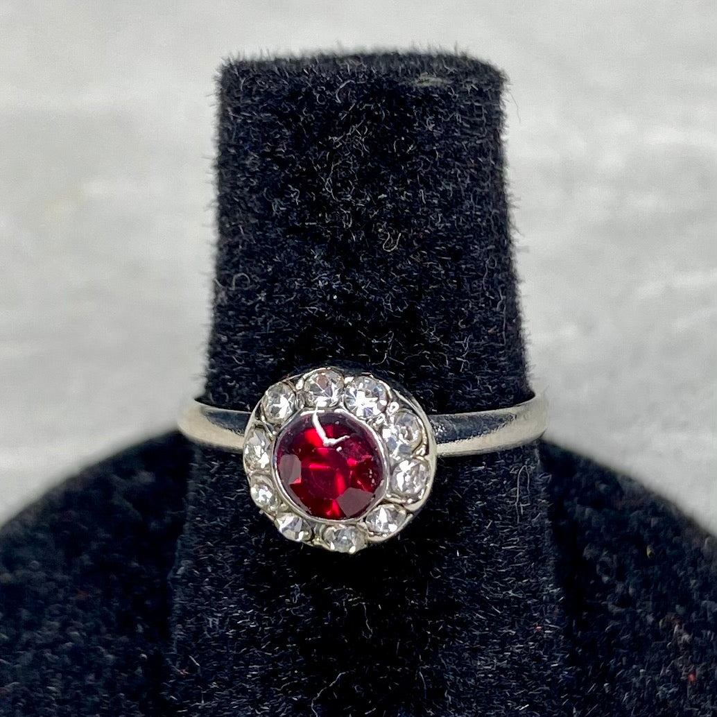 Red center gemstone surrounded by white gemstones on an adjustable silver band.