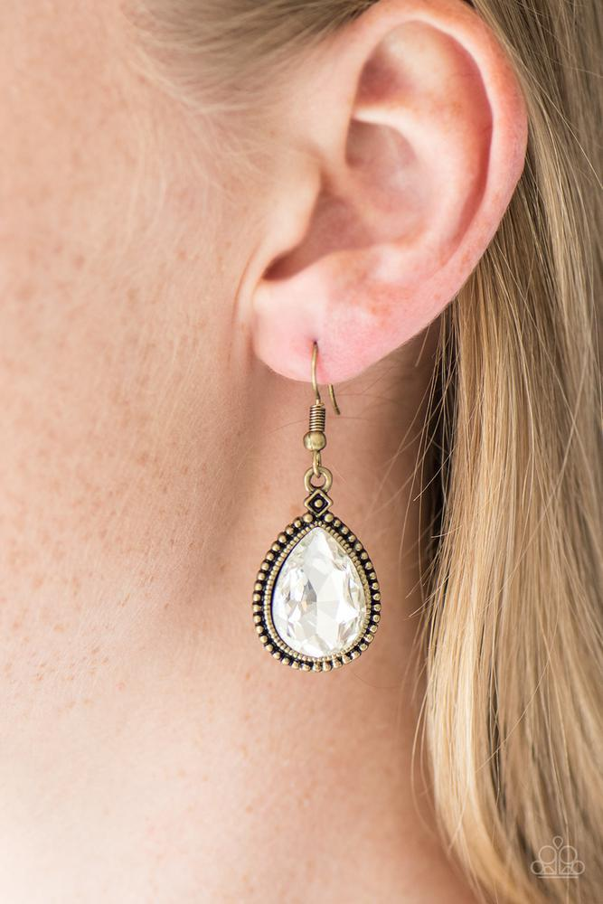 A glassy white teardrop is pressed into a studded brass frame, creating a regal lure. Earring attaches to a standard fishhook fitting.