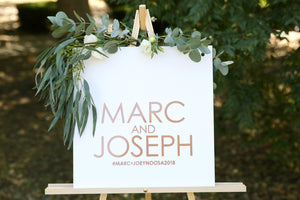 Rose gold on white wedding sign on easel