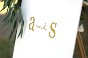 Close up of monogram wedding sign - gold and white