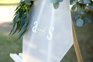 White and frosted monogram wedding sign, on easel