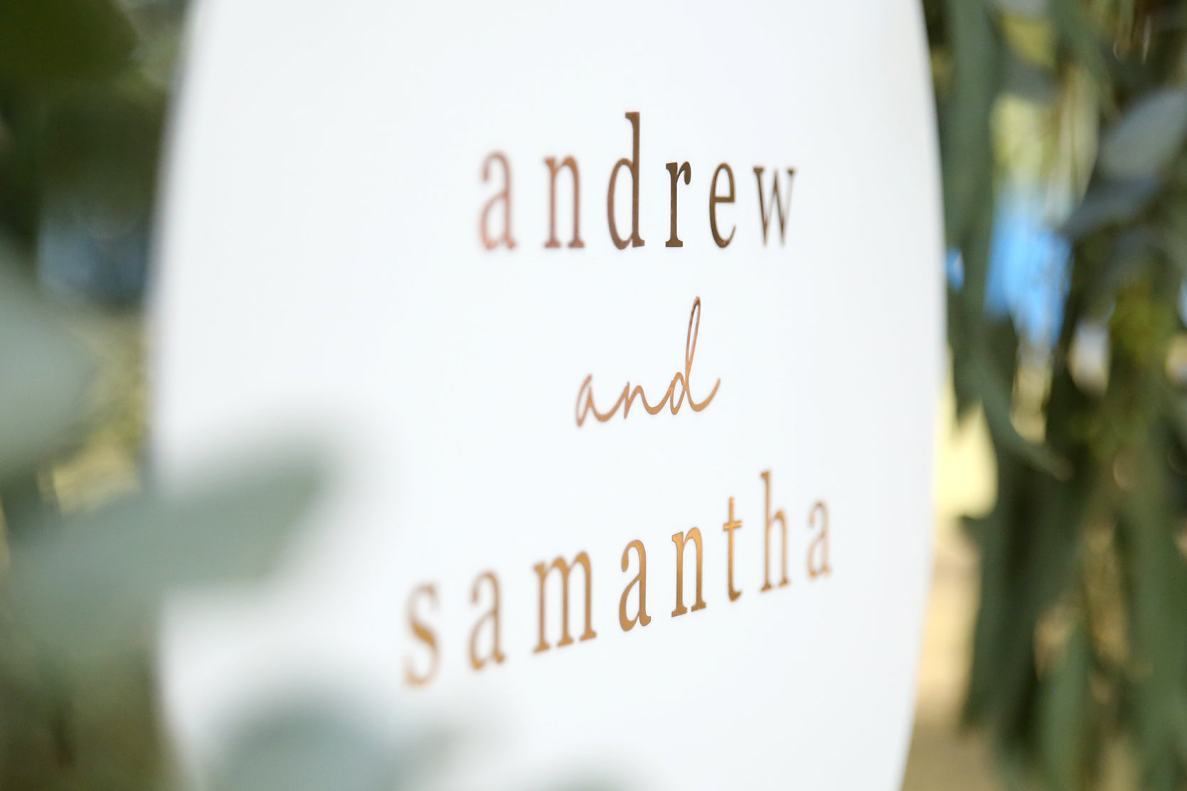 Close up of white and rose gold wedding sign