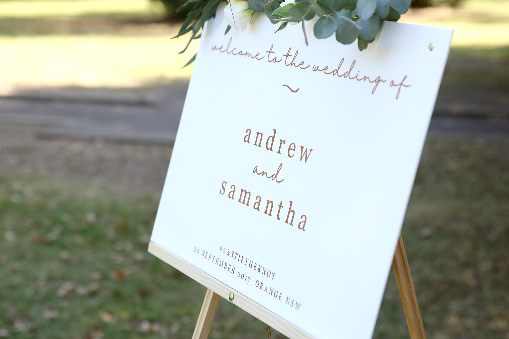 Scripted wedding sign displayed on an easel