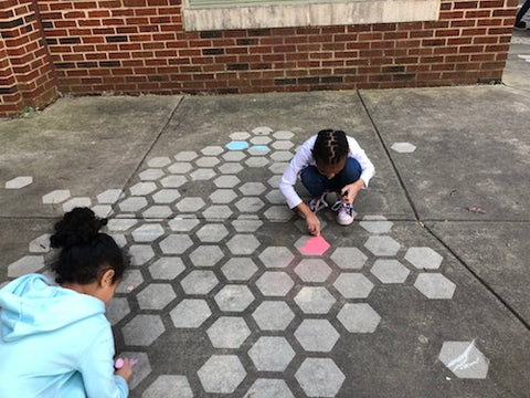 Kids coloring their Driveway Art CLT Hive design with sidewalk chalk