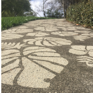 Woman showcasing the Concrete Jungle Stencil from Driveway Art®.