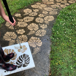 Woman standing on top of the Concrete Jungle Stencil from Driveway Art® and pressure washing the stencil to make a pattern in the dirt.