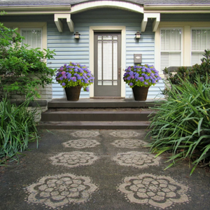A yellow electric pressure washer, Driveway Art® Mandala stencil and pressure washed pattern in front of a blue bungalow house.