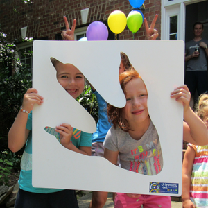 Two kids holding the T-Rex Stencil from Driveway Art® with colorful party balloons in the background.