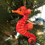 adorable hand-painted red seahorse ornament hanging on Christmas tree with lights