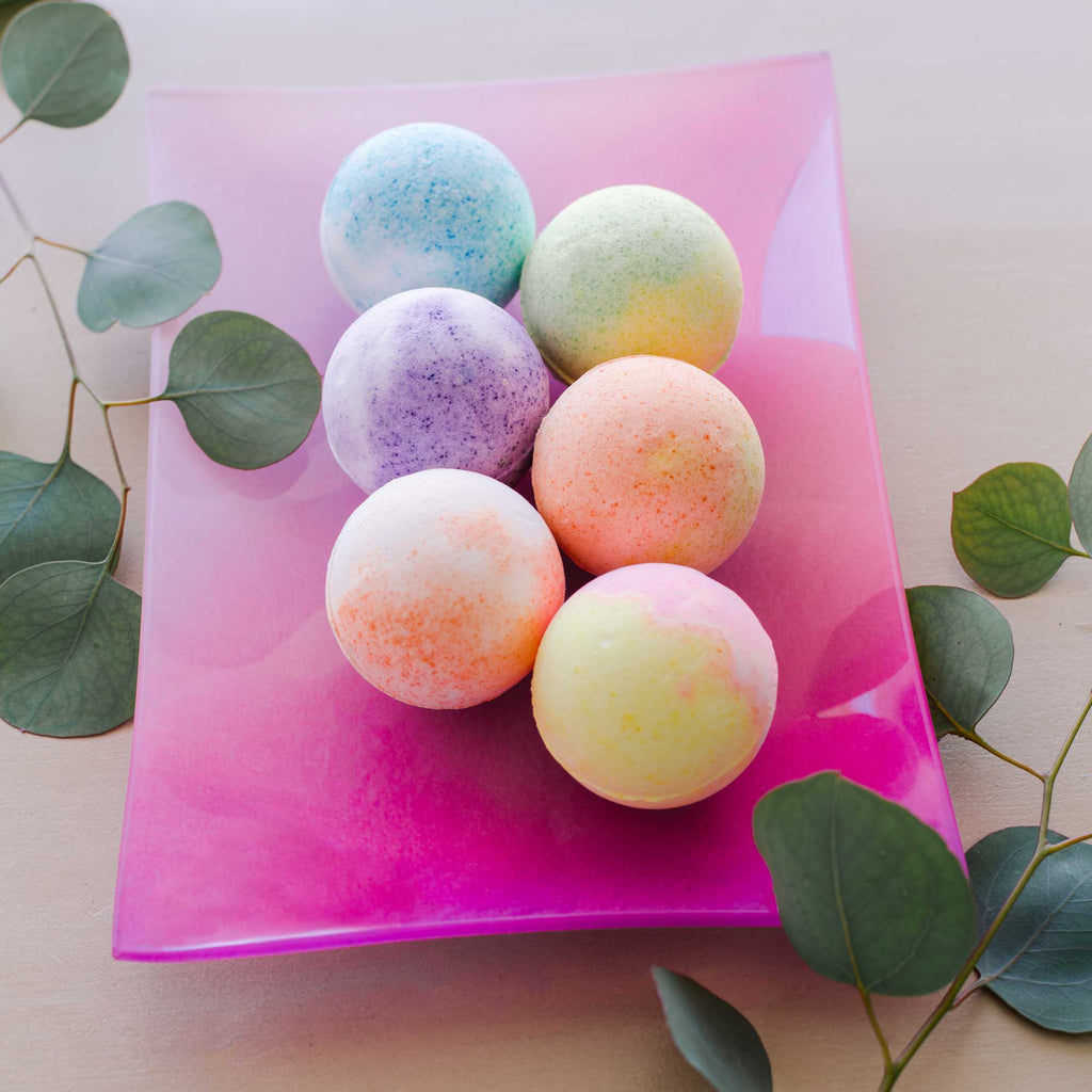 rengora's large fragrant 4oz bath bombs (6) on beautiful pink glass plate with eucalyptus leaves
