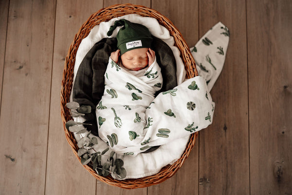 newborn baby swaddled in the cactus print muslin wrap by snuggle hunny kids