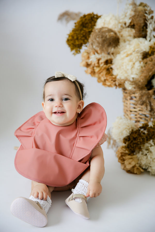 snuggle bib by snuggle hunny kids in terracotta colour on a bubba