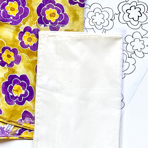 A pattern kit includes a white silk scarf to paint on.