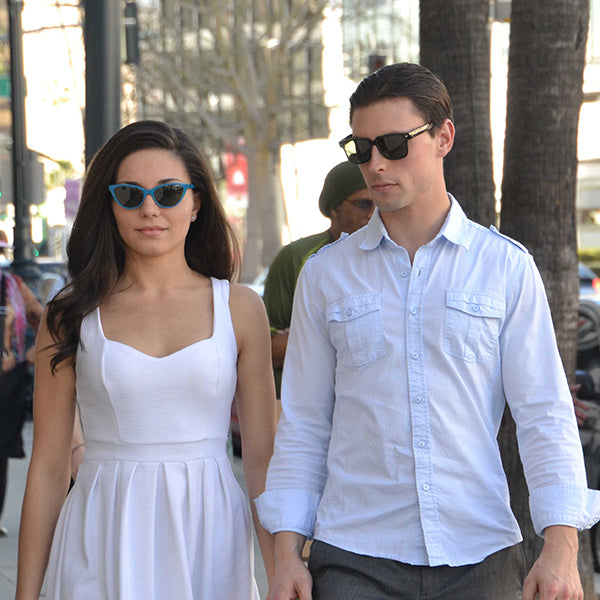2 People wearing blue and black cat eye sunglasses.