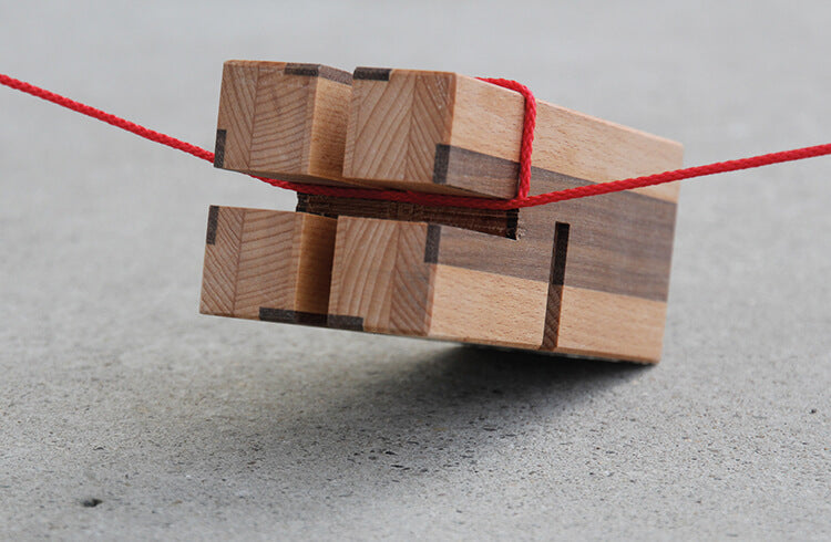 A red string is wrapped around a notched wooden block from Metalog Tools' Tower of Power, a top team building tool and training activity