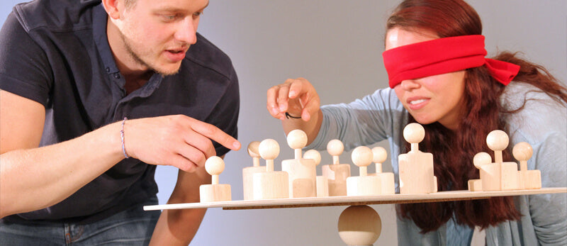 A man tells a blindfolded woman how to move a figurine in Metalog Tools SysTeam, an active listening exercise to build trust