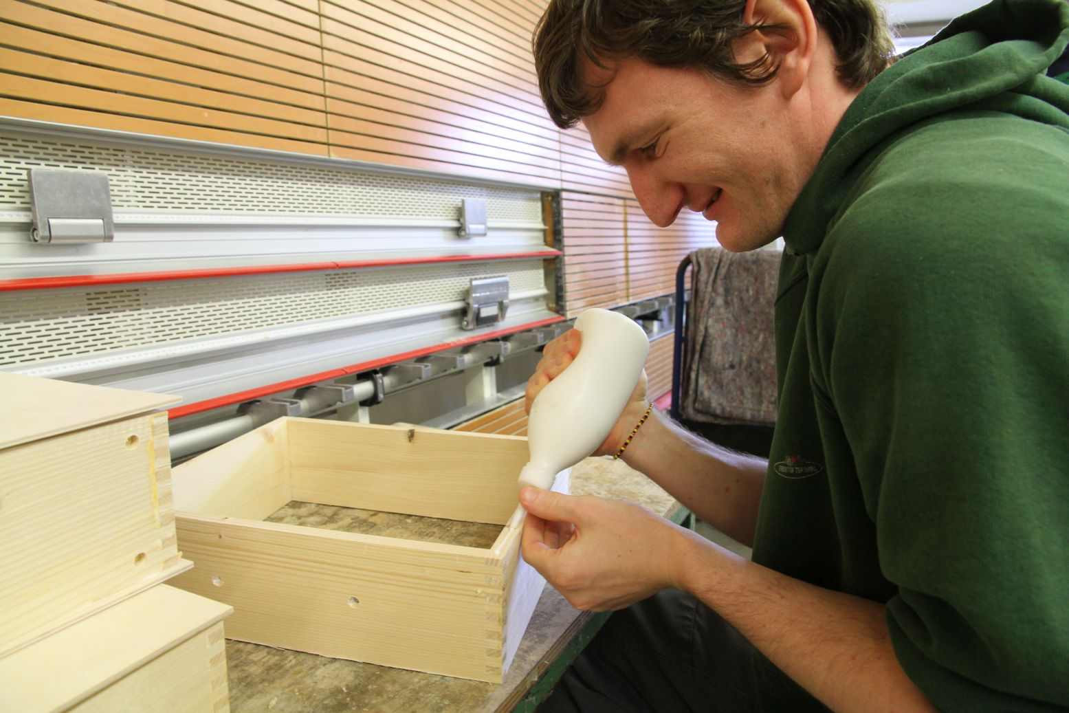 A man at a workshop for skilled workers with disabilities glues a wood box for Metalog's collection of sustainable training tools