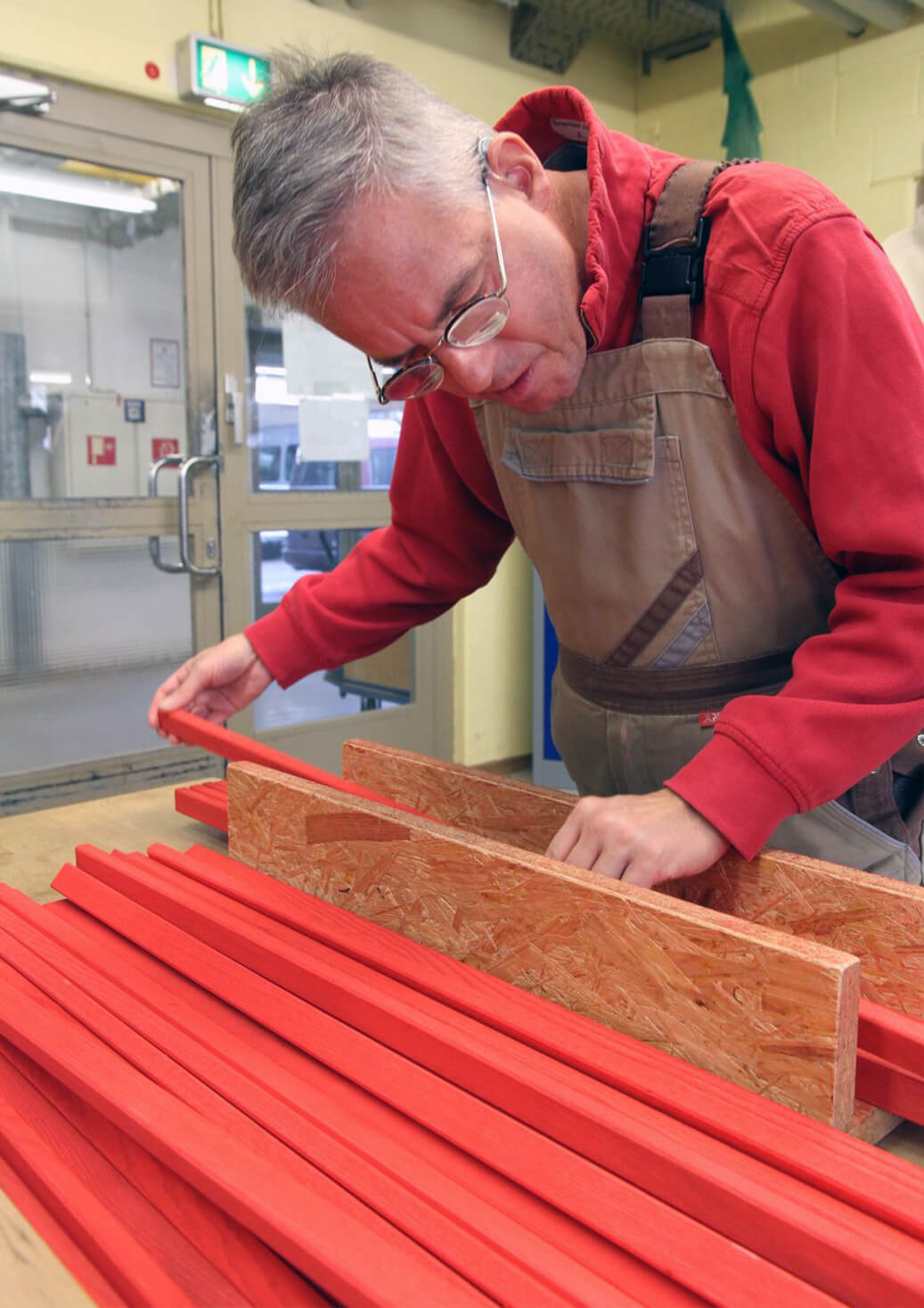 A man wearing an apron inspects red wooden boards that will be crafted into Metalog tools for use in hands on training activities