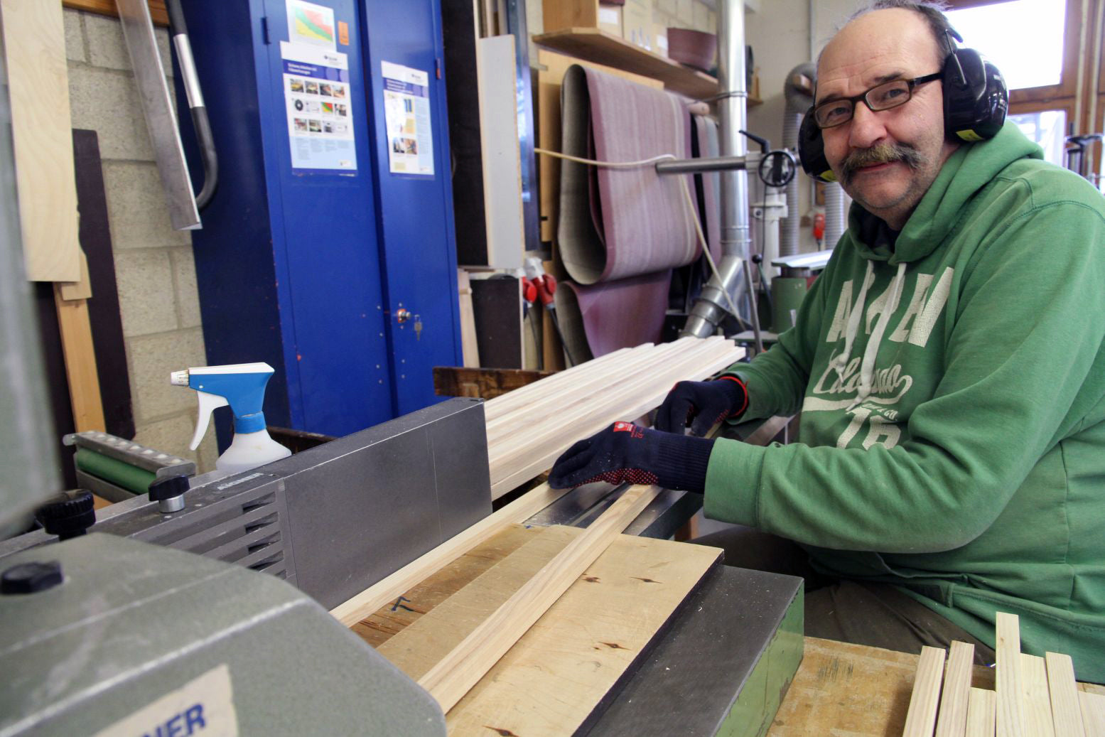 A man in a workshop uses a machine to plane and sand raw wood for Metalog Tool's award-winning and sustainable training tools