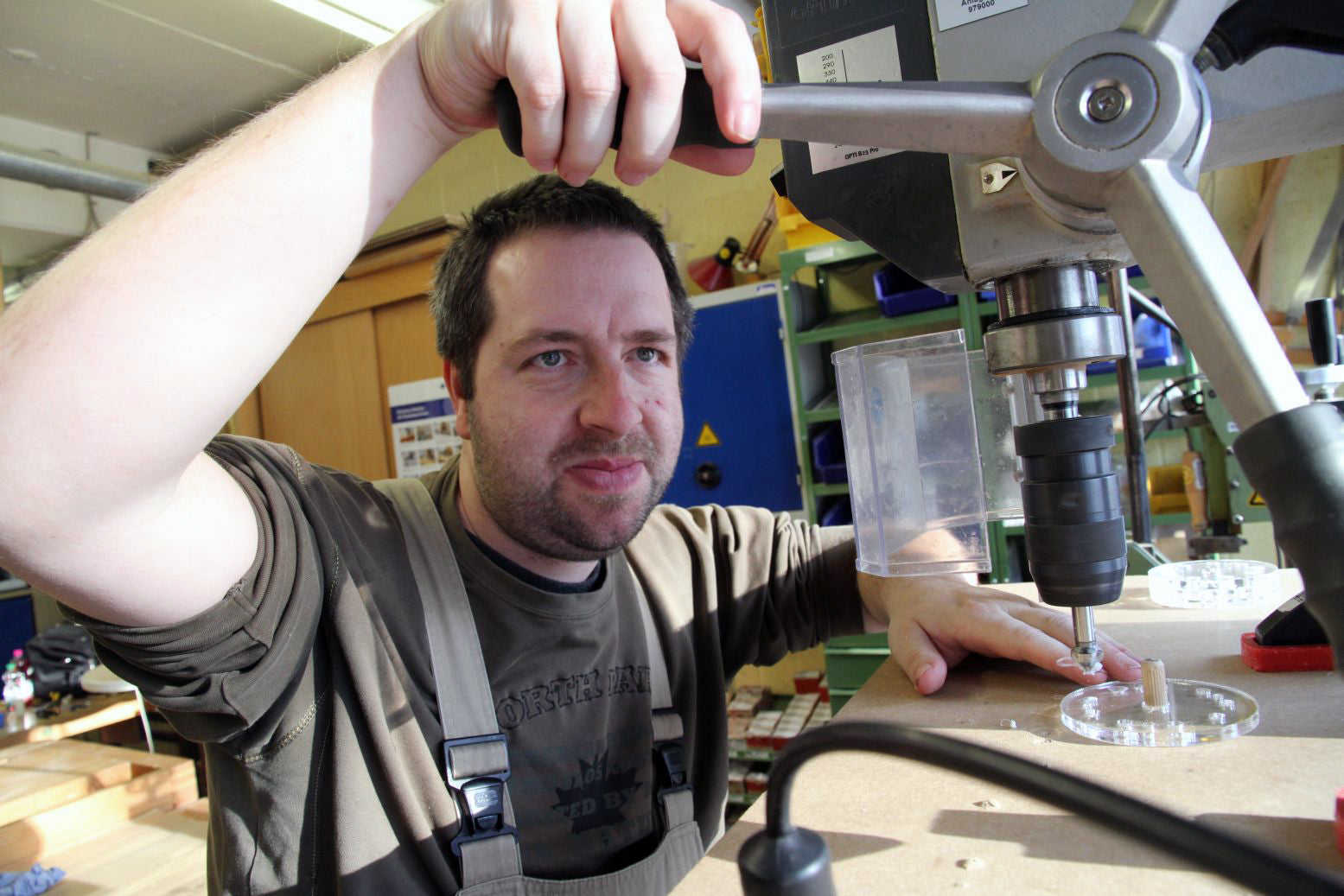 A man wearing an apron uses a drill press to build a training tool for Metalog, a top brand for experiential learning activities