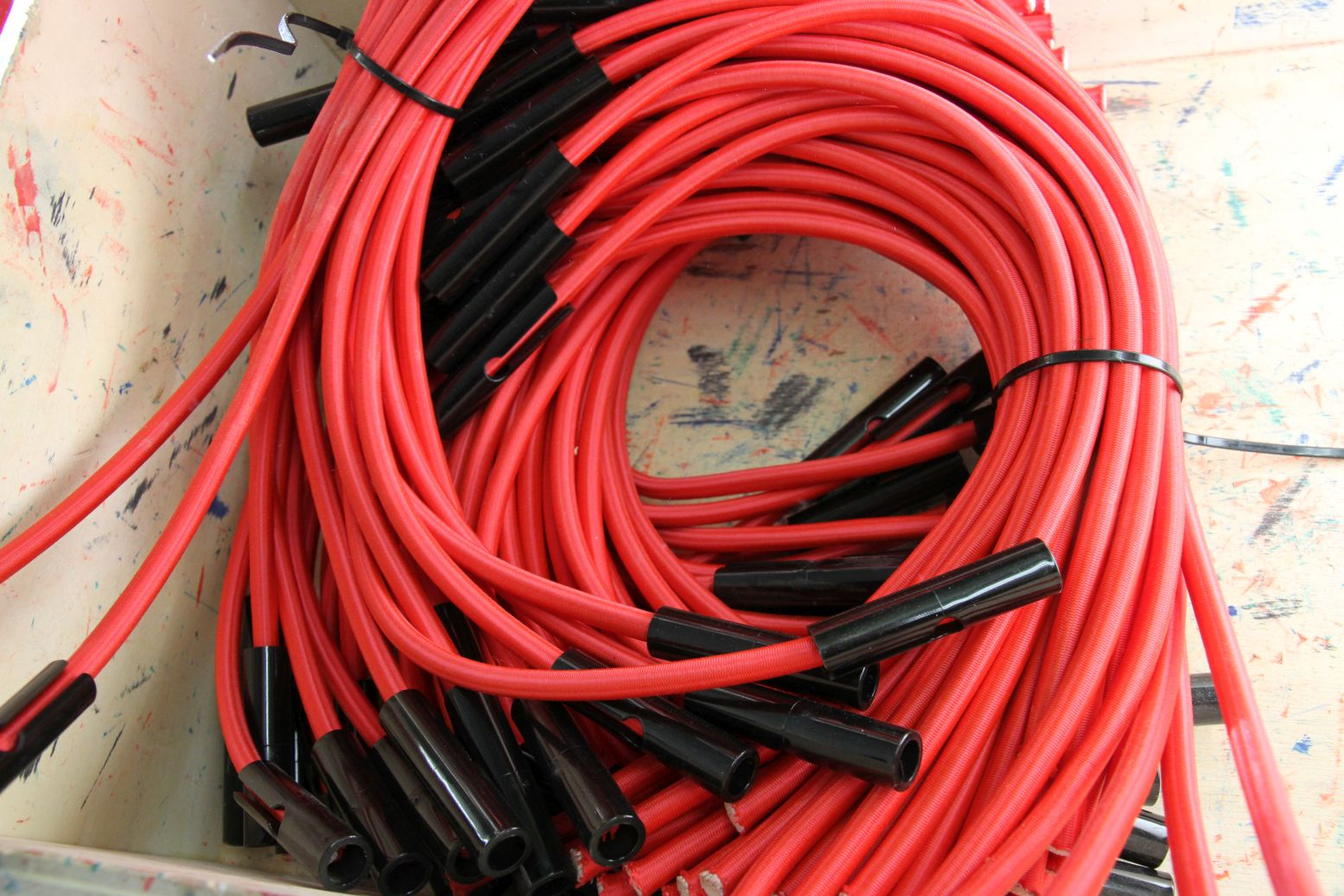 A pile of red tubing with black fasteners will be constructed in a Metalog Tools experiential learning activity or game