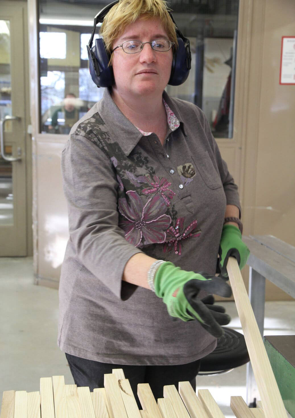 A female Metalog Tools employee wearing green gloves selects a raw birch wood board to be handcrafted into a team building tool